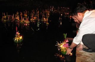 A couple putting their kratong in the water at Bang Wad Reservoir