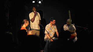 Tostan's Seydou Niang (standing) presents about Tostan France during the concert. Volker (seated, left), Seydou (standing, back), Percussionist Joe Quitzke (seated, middle), and Cissokho (seated, right).