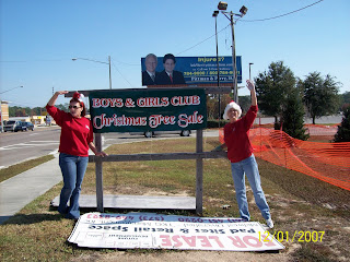Joanie Miller and Kate Courtney waving at drivers as they pass the Boys and Girls Club sign in front of Sam's Club