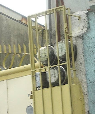 electricity meters in a padlocked metal cage