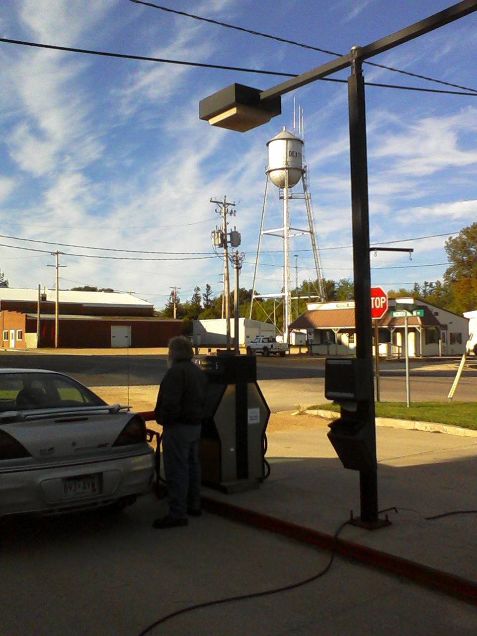 nick s photo essay small town life 2010 jim owner and mechanic at dexter mobil fills a customer s car above him rises the town s water tower