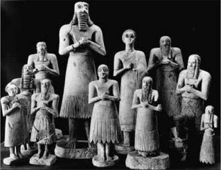 Sumerians Worshipping Abu, God of Vegetation. This group of marble votive statues (the largest is thirty inches high and probably represents the local king) was carved at Eshnunna in southern Mesopotamia between 2700 and 2500 B.C. The figures were placed around the altar and were expected to serve as perpetual stand-ins for their donors. The huge, staring eyes reflect the rapt attention expected by the god.
