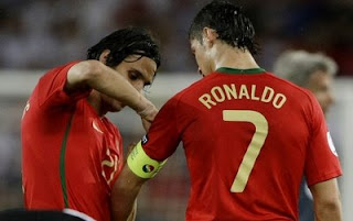 Nuno Gomes fixes the captain's armband onto the arm of Cristiano Ronaldo after he was substituted during their Euro 2008 quarter-final soccer match against Germany