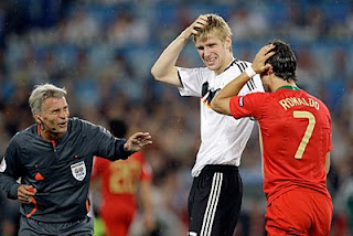 referee Frojdfeldt checks on Mertesacker and Ronaldo after a clash of heads.
