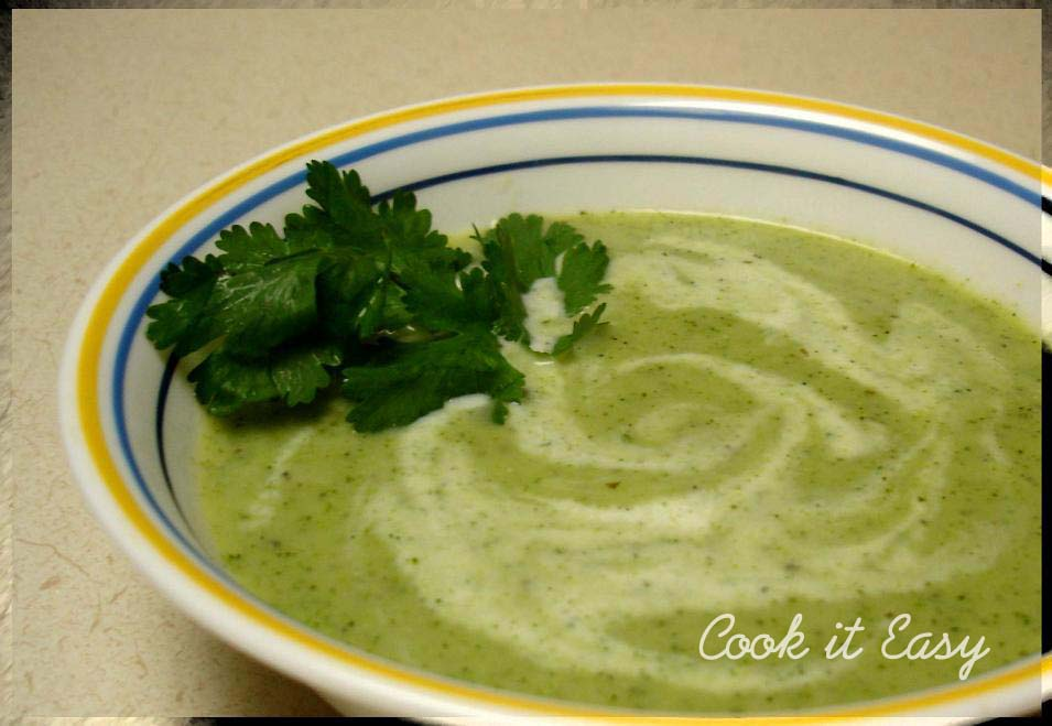 Cream of broccoli soup with a dash of cream added on top & garnished ...