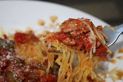 bowl of spaghetti squash shreds with ground turkey and parmesan cheese covered in vegetable ragu red sauce, fork picking up a piece from the bowl