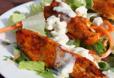 plate of lettuce and shredded carrots with buffalo chicken and blue cheese dressing