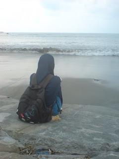 seorang perempuan memandang laut dengan sendu
