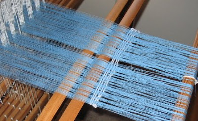 A few picks woven in behind the heddles.