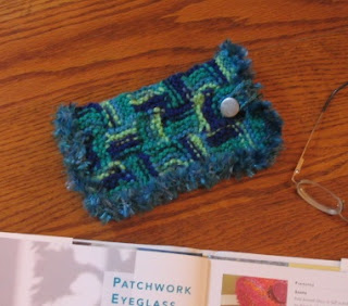 Patchwork eyeglass case of modular knitted squares.
