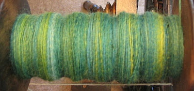 Painted roving singles on the bobbin.