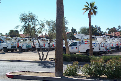 A large number of Cox cable repair trucks parked in front of a hotel at a different angle.
