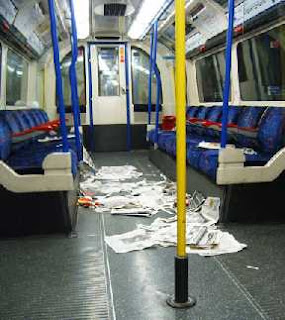 A tube carriage strewn with discarded newspapers