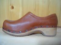 artigiano che produce scarpe con suole in legno personalizzate