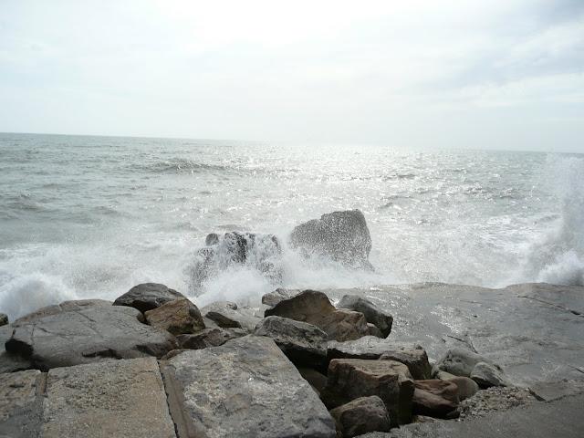 El mar rompiendo sobre rocas en la playa.