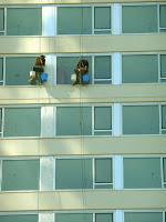 Dos lavadores de vidrios de ventanas en altura en edificio de departamentos.