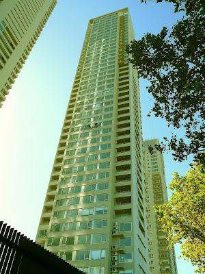 Un edificio gigante de departamento con dos personas trabajando en altura.