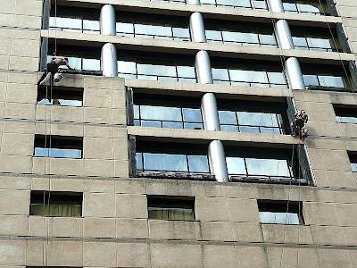 Dos personas limpiando los vidrios en altura del frente de Edificio.