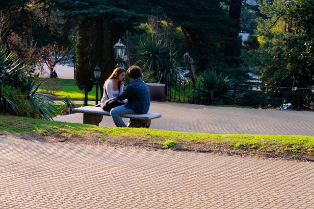Gente,pareja enfrentados en banco de plaza.