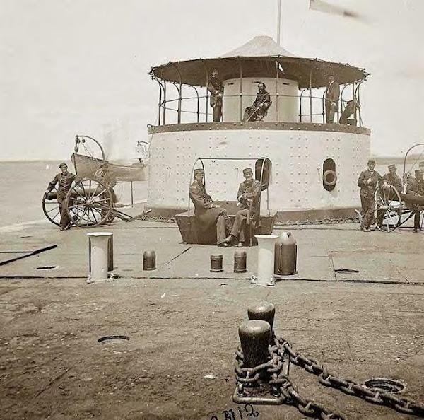USS Monitor Catskill. Lt. Edward Barrett seated on turret. Charleston Harbor, SC. 1865