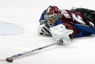 Jose Theodore pokes the puck away as he posts up a shutout in the Colorado Avalanche's 2-0 win over the Calgary Flames