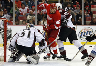 Tomas Holmstrom of the Red Wings tries to deflect a shot past Peter Budaj of the Avalanche