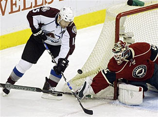 Andrew Brunette of the Colorado Avalanche has the puck swept away by Nik Backstrom of the Minnesota Wild during a game on March 17, 2007