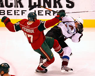 Peter Forsberg of the Colorado Avalanche collides with Todd Fedoruk of the Minnesota Wild during a playoff game