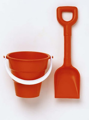 Red plastic bucket and spade for beach sands