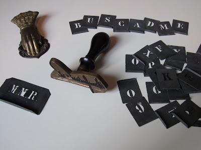Tres objetos de escritorio que conservo de mi abuelo: sujetapapeles de latón, sello de bronce con su firma, y moldes de letras de latón.