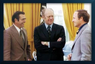 Ford smiles down on his Chief-of-Staff Don Rumsfeld and his Deputy Dick Cheney.