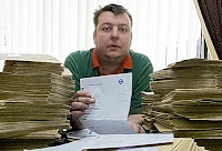 Graeme Ellis opens some of the 3,000 receipts TfL sent him for his congestion charge