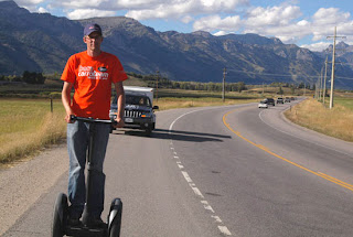 John riding the Segway on their 10 MPH road trip