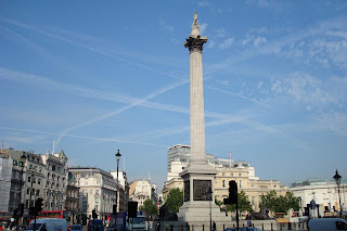 Vapour trails in sky over Trafalgar Square, London