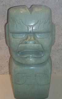 """4eb9a22656a5 Hacha ceremonial de jade translúcido. Forma parte de los objetos típicos  olmecas. A la nariz chata y la característica """"boca olmeca"""""""