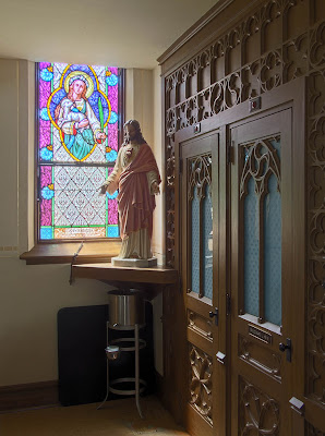 Immaculate Conception Roman Catholic Church, in Augusta, Missouri, USA - stained glass window of Saint Agnes; statue of Sacred Heart of Jesus; confessional