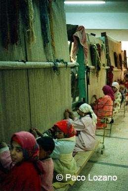 Niños tejiendo alfombras