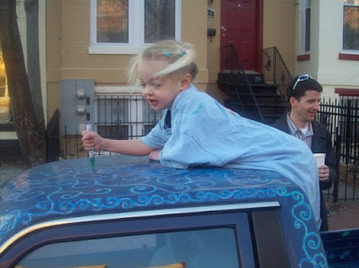 blonde 3-year-old in pigtails drawing on the roof of the cab
