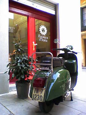 Puerta de entrada a la Enoteca d'Italia con una Vespa aparcada en frente