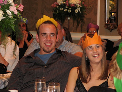 bride and groom listening to speeches, while wearing their paper crowns