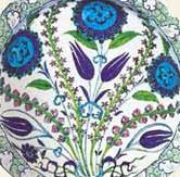 An Iznik late, c.1550, decorated with tulips and hyacinths bound together with lotus flowers, showing the distinct Chinese influence of Iznik pottery