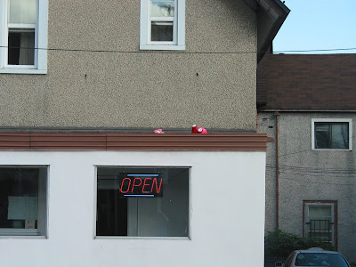 two pink teddy bears on top of a roof