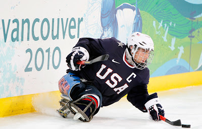 Andy Yohe carries puck during Ice Sledge Hockey on day two of 2010 Winter Paralympic Games