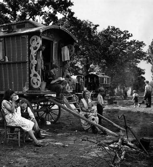family of gypsies sitting outside their caravan on an encampment