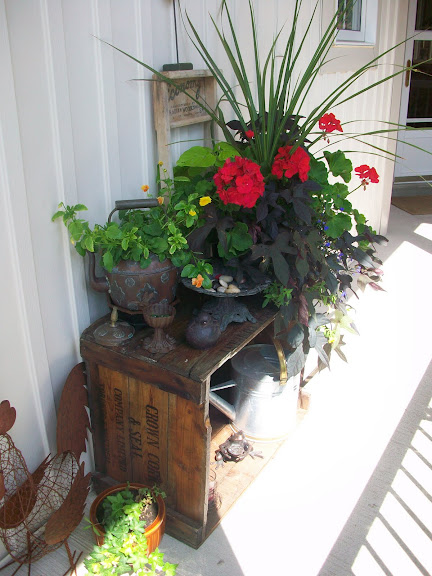 Flower pots on top of a vintage crate for a front porch.