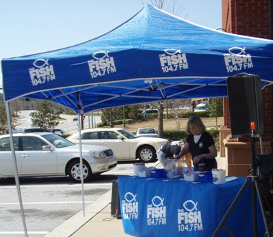 104.7 THE FISH setting up and giving away goodies to those who stopped by.
