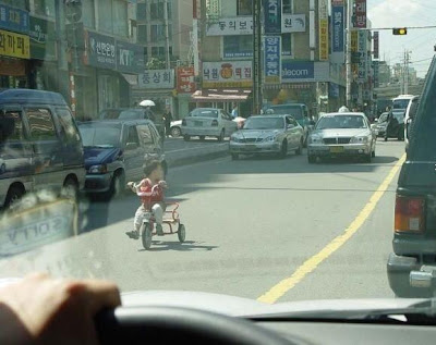 Kid riding tricycle in traffic