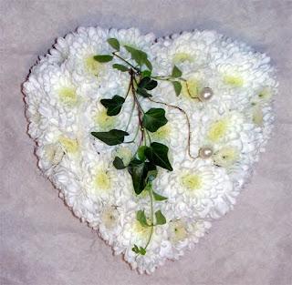 Fehér virágokból készült esküvői gyűrűpárna szív alakú