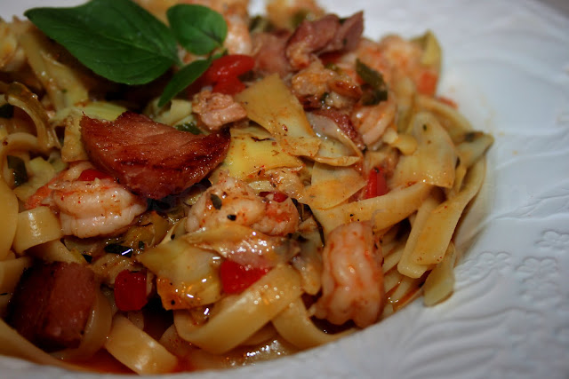 My Mama's Shrimp and Fettuccine recipe, made with shrimp and andouille sausage, cooked in a buttery sauce tossed with fettuccine, fresh herbs, artichokes and pimentos.