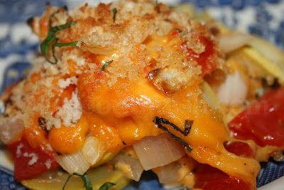 A squash and tomato casserole, layered in a pan with sweet Vidalia onions, bacon and cheese, and seasonings, topped with panko bread crumbs and garnished with a chiffonade of fresh basil.